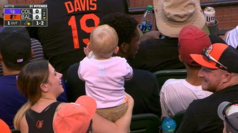 COL@BAL: Baby winds up with baseball in the stands